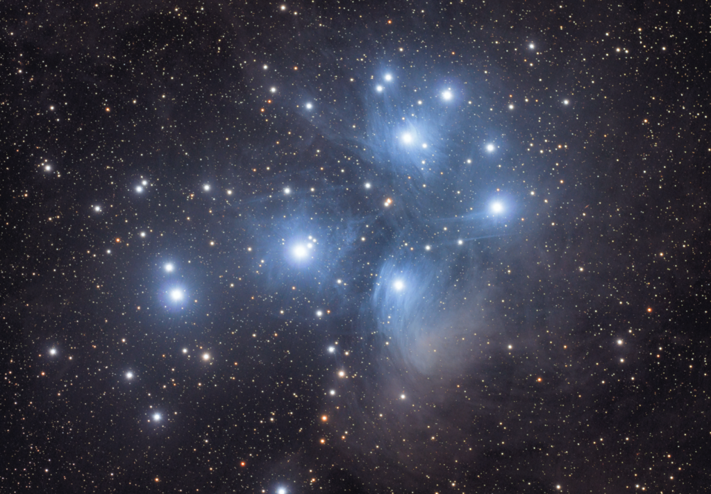 Bright bluish young stars standout against a background of fainter more distant stars. A nebulous haze glows faintly around them, suggesting this is a very young cluster of stars.
